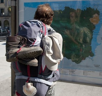 A pilgrim obtains information from a panel in Ribadeo